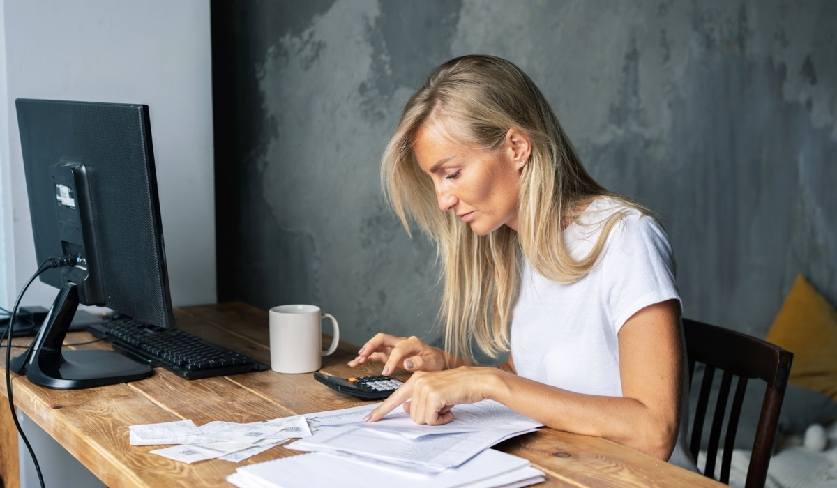 Woman reviewing invoices at her desk.