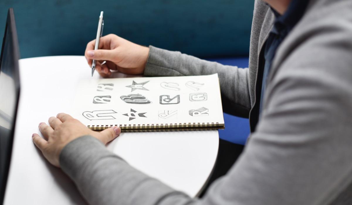A designer sketching logos on a sketch book.